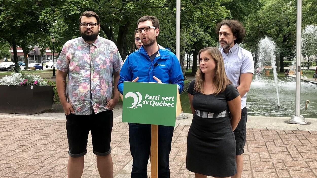 Le chef du Parti vert du Québec au podium dans un parc, entouré de candidats