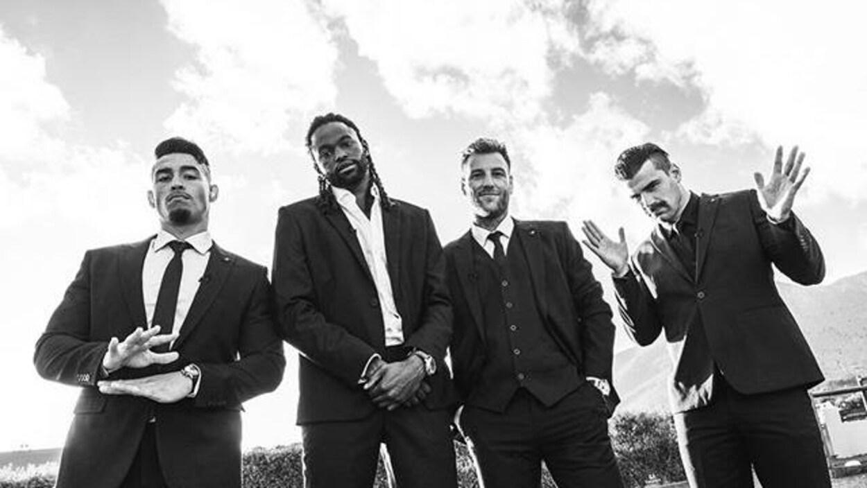 Les quatre hommes sont habillés en costume et regardent le photographe.