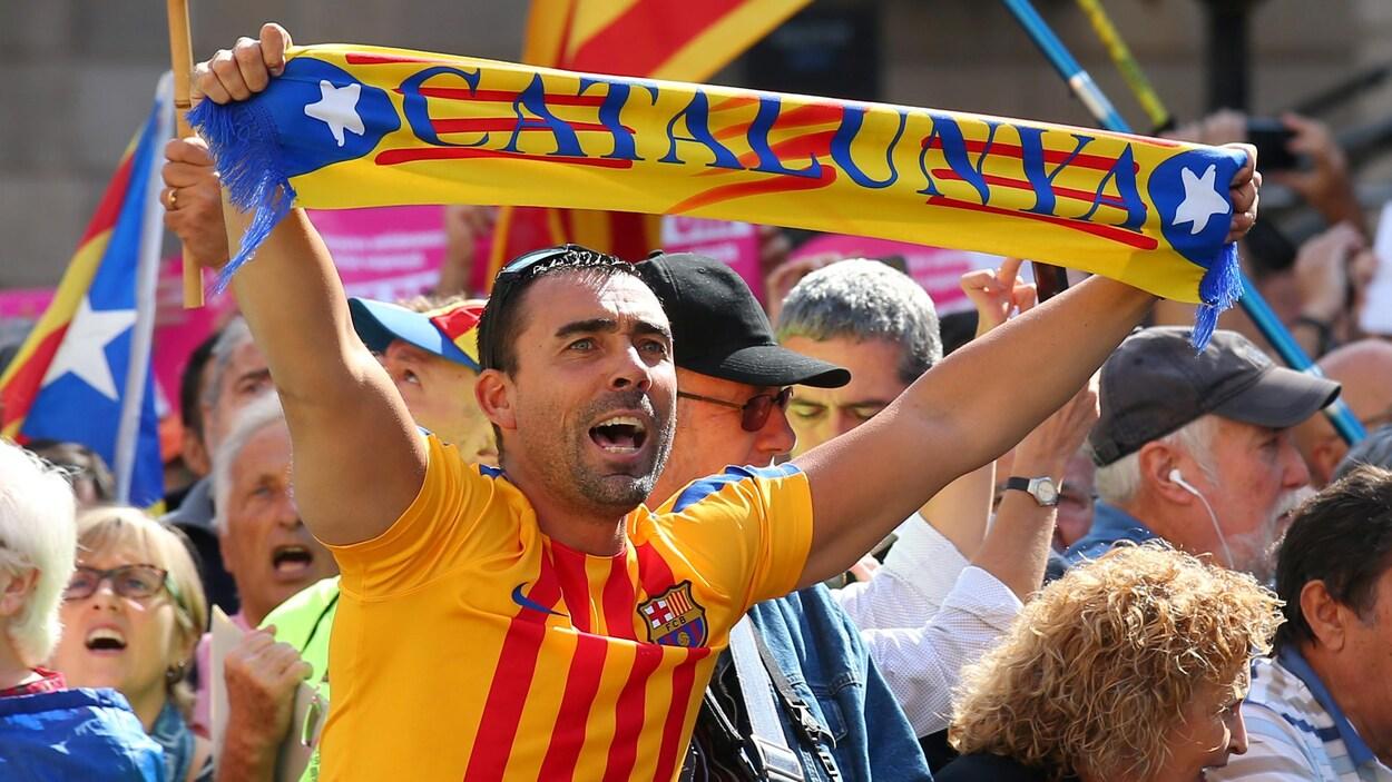 Un indépendantiste brandit un foulard sur lequel est écrit Catalogne durant la manifestation des maires à Barcelone.