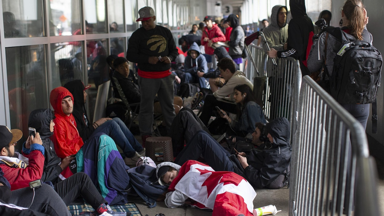 Des partisans des Raptors debout et couchés au sol, en file pour avoir une place au Jurassic Park.