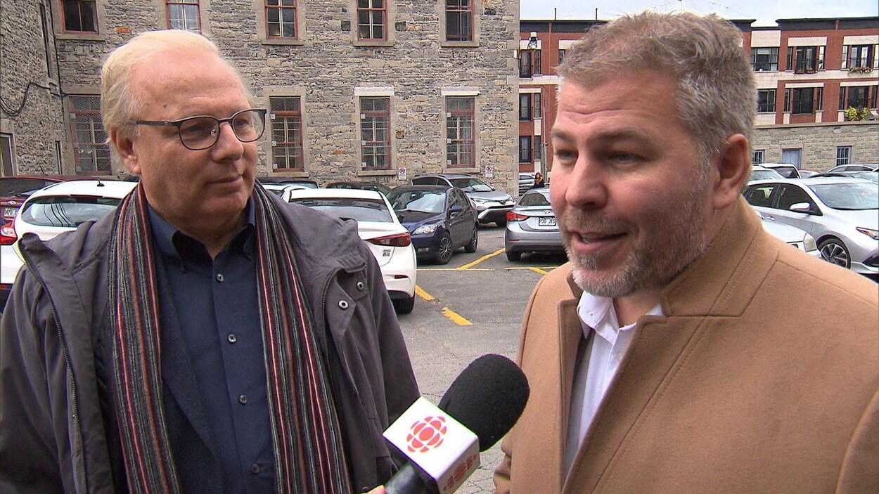 Deux hommes répondent aux questions au micro dans un stationnement du Vieux-Montréal