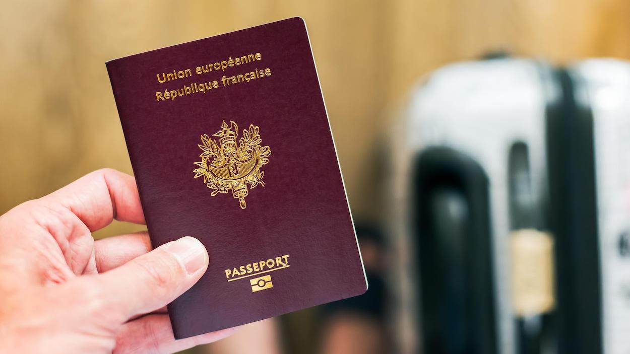 Un homme tenant un passeport français.