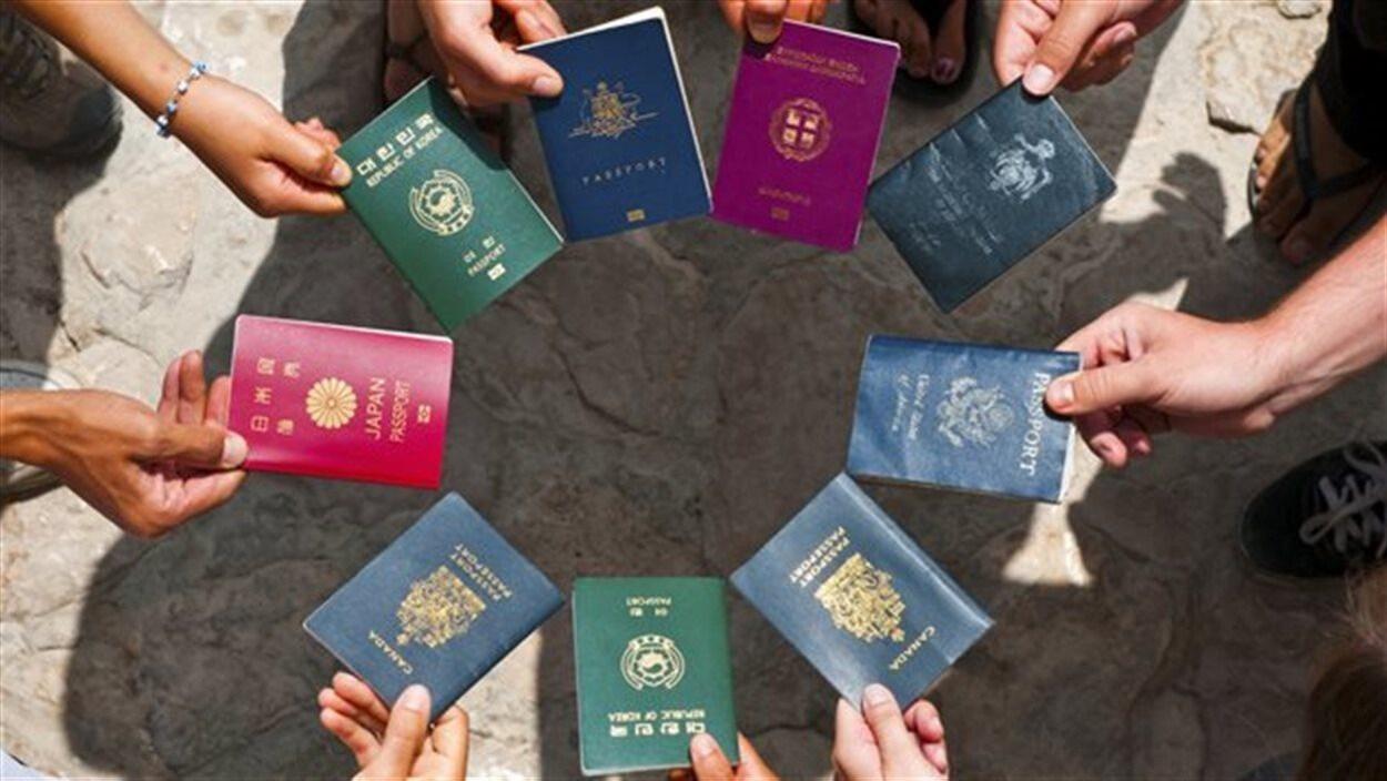 Neuf mains tiennent chacune un passeport de pays différent.