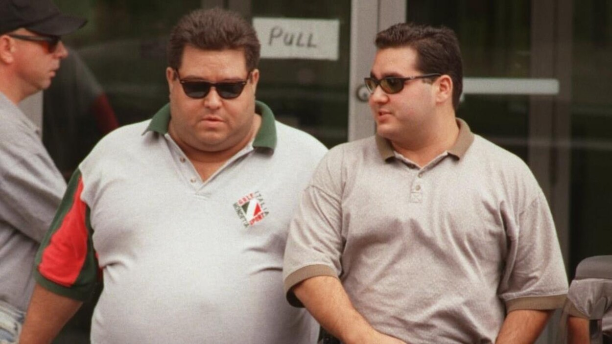 Deux hommes marchent sur un trottoir.