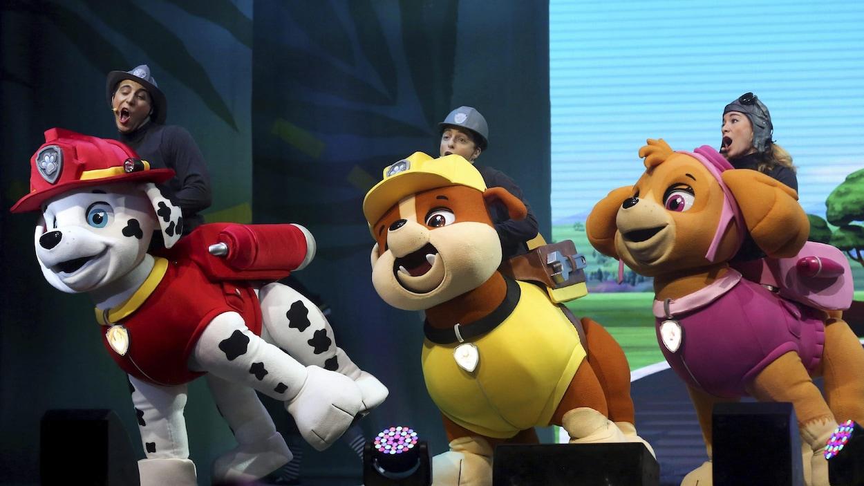Des comédiens contrôlent des marionnettes géantes à l'effigie des petits chiens de la série.