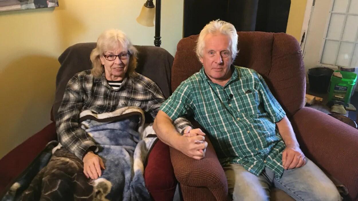 Le couple assis dans des fauteuils se tient par la main