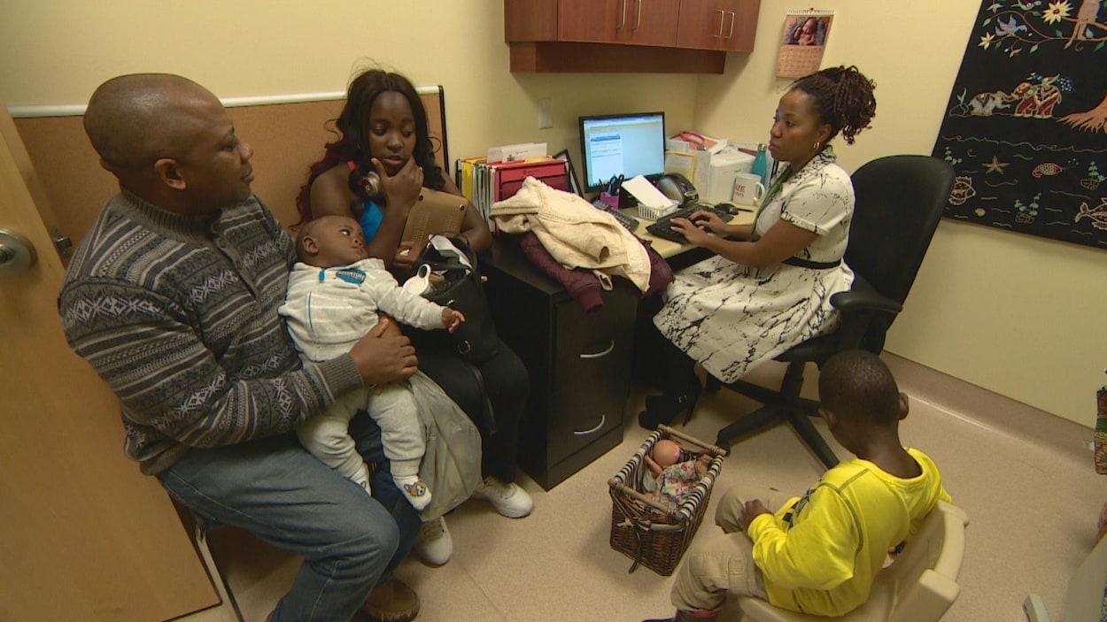 Un père une mere un bébé un bambin dans le bureau d'une infirmière