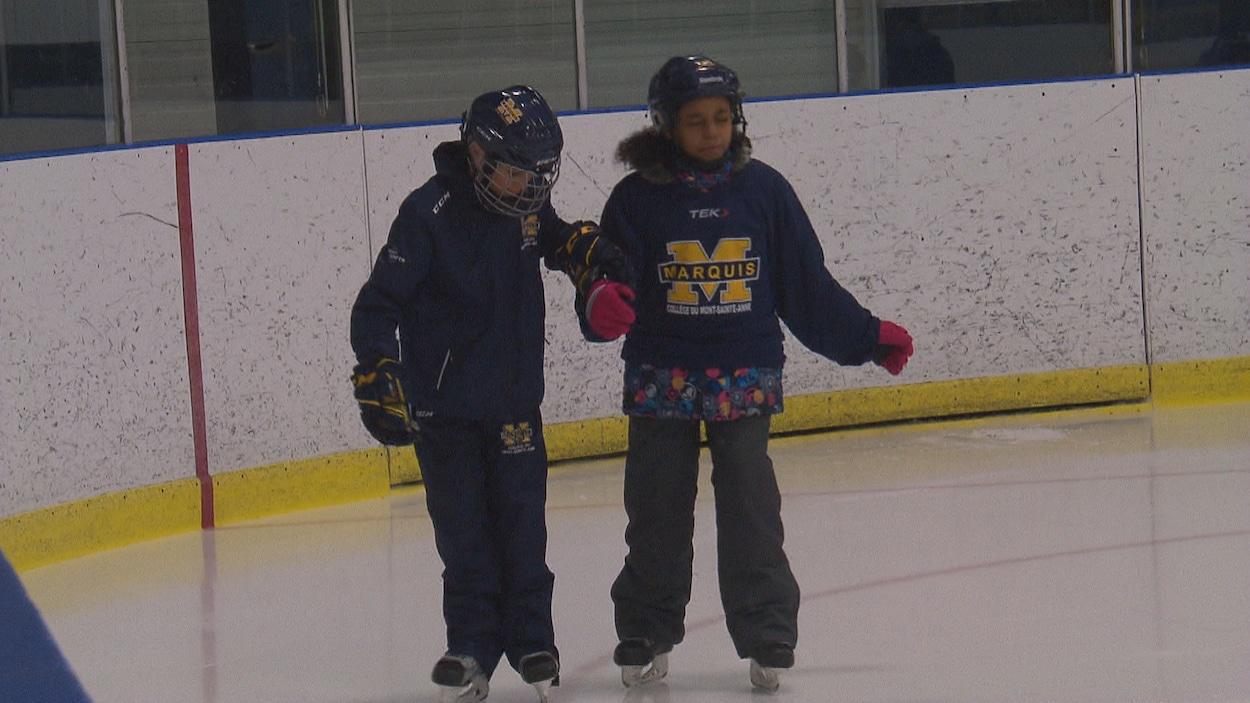 Deux enfants patinent ensemble.