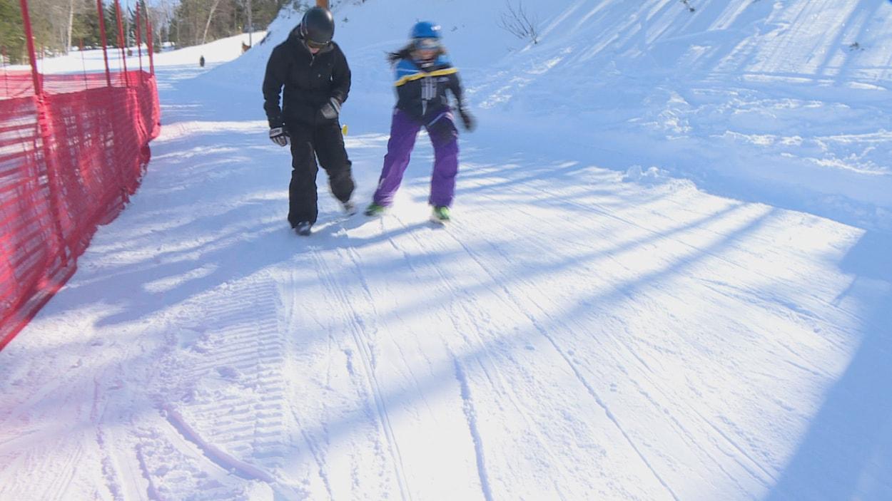 Deux personnes en patins à neige sur une piste de ski