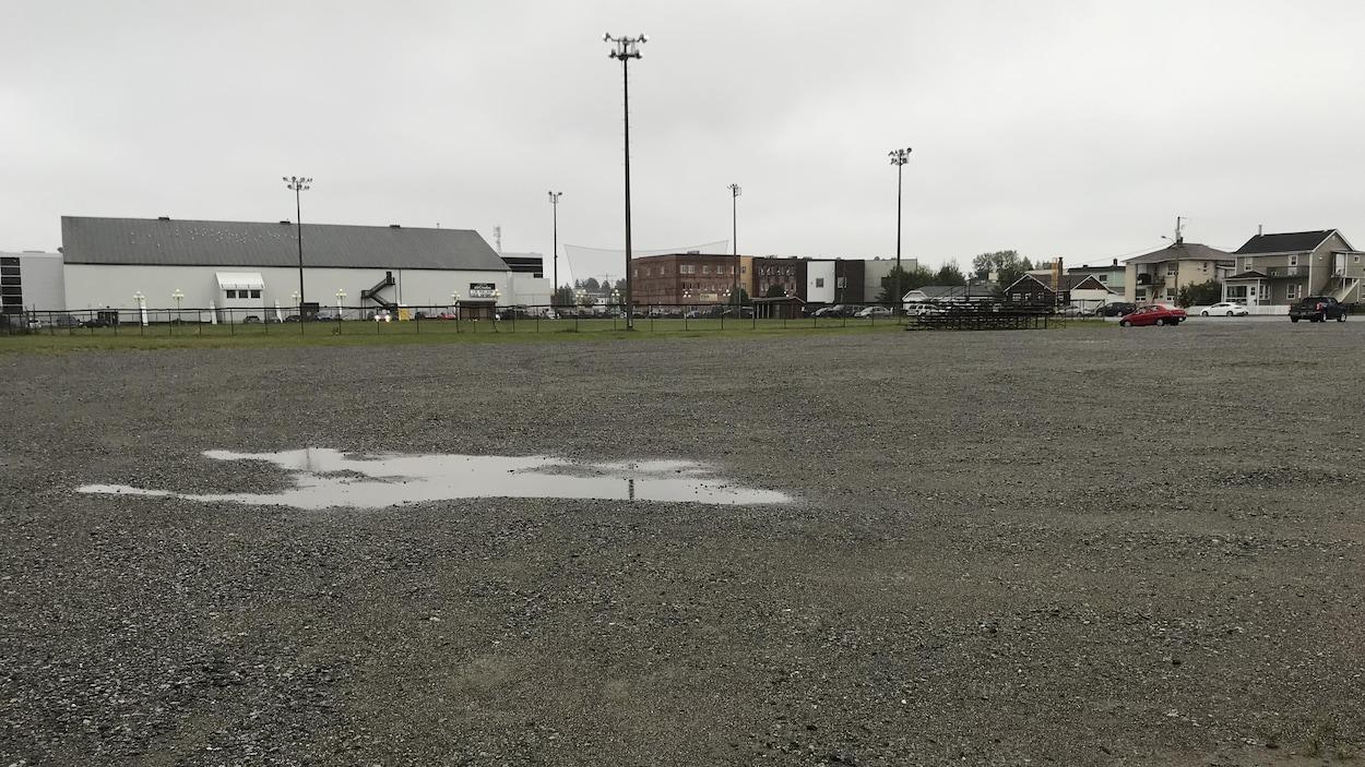 Une terrain vague, vide, en gravier, à côté d'un bâtiment blanc.