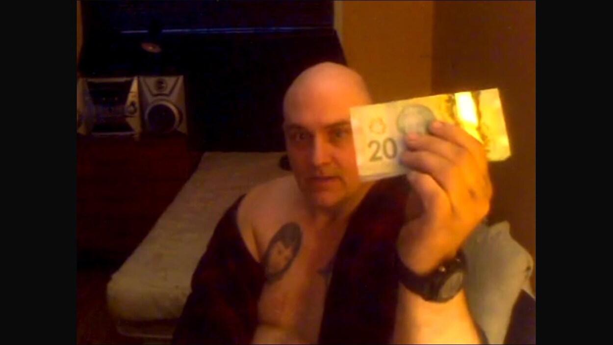 L'homme au crâne dégarni, vêtu d'une robe de chambre, exhibe une liasse d'argent à la caméra.