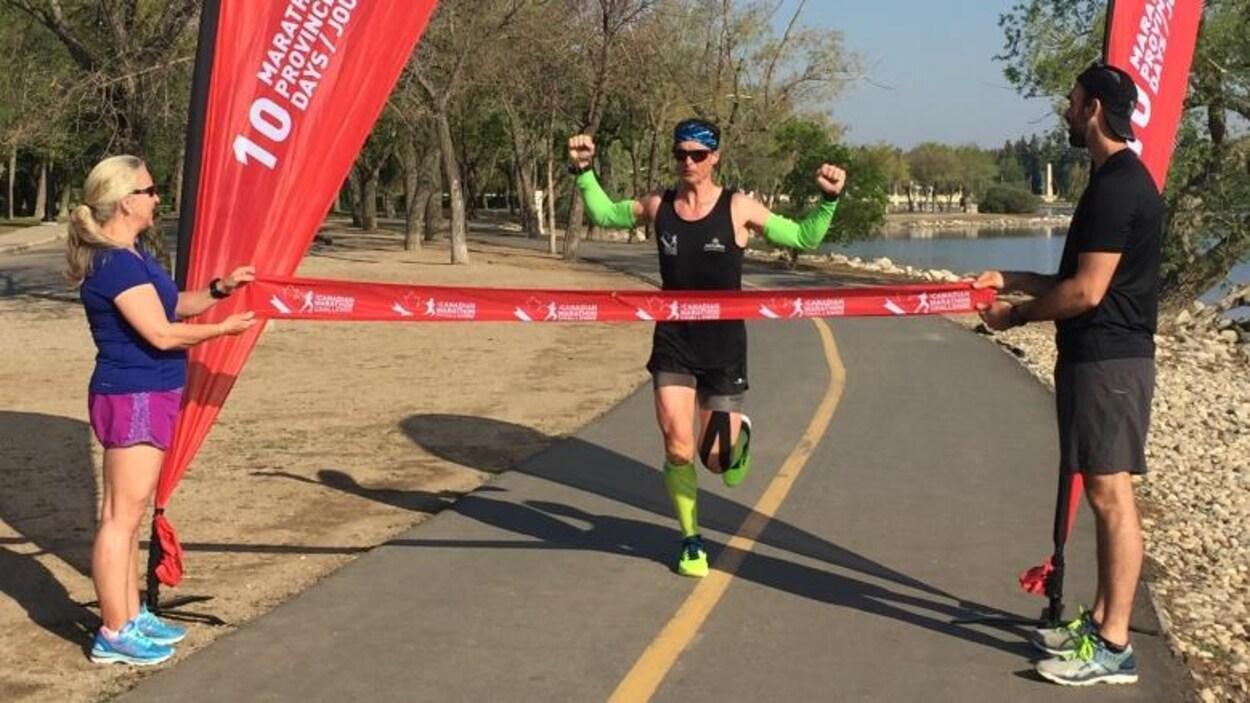 Patrick Charlebois termine son marathon autour du lac Wascana à Regina en levant les bras à la ligne d'arrivée sous un ciel bleu.