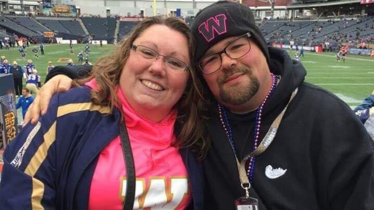 Une femme et un homme, Danielle Vandale et Patrick Gagnon. sourient à la caméra. Ils sont dans le stade de football des Blue Bombers à Winnipeg et portent des vêtements aux couleurs de leur équipe.