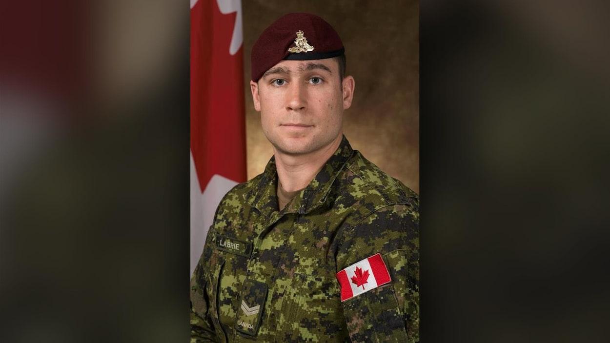 Le bombardier Patrick Labrie pose devant un drapeau canadien.