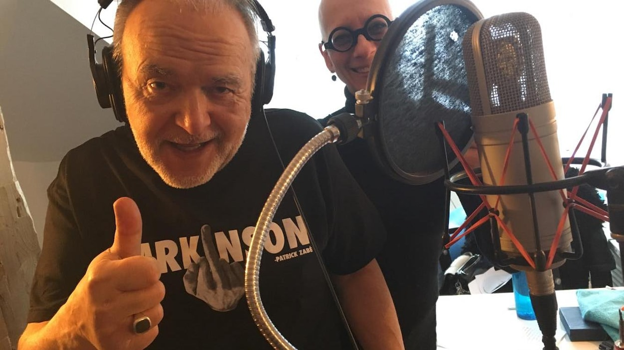 Patrick Zabé au studio The Trench de Québec lors de l'enregistrement de la pièce « Le zéro du texto ». On l'aperçoit devant un micro, heureux et légèrement voûté. Sa femme est à ses côtés.