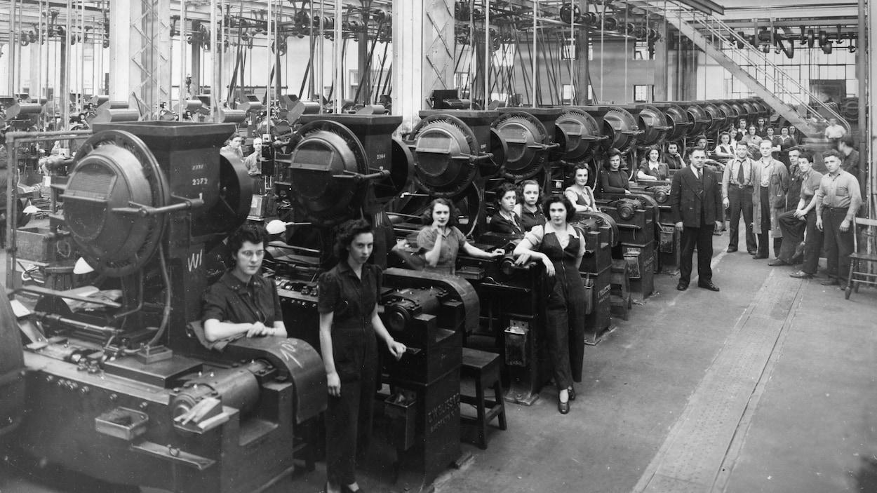 Des hommes et des femmes sont adossés à des machines dans cette photo en noir et blanc.