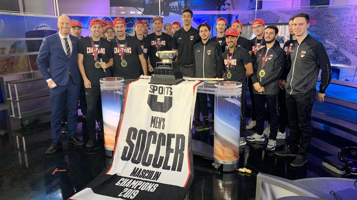 L'équipe sur le plateau avec le trophée et la banderole de la victoire.