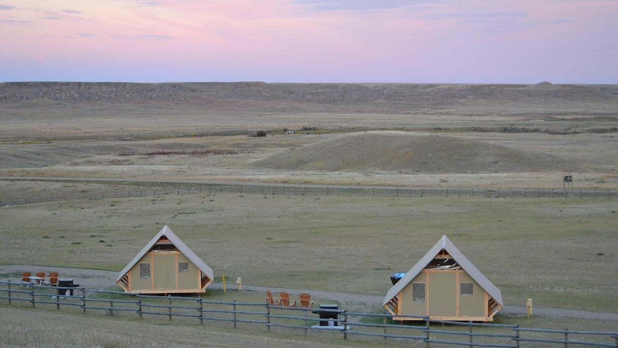 Vue sur deux cabanes dans les prairies, à la tombée du jour.