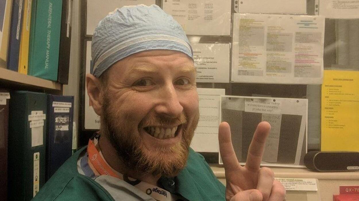 Paul Bennett qui a été tué par balle à Surrey fait un signe de la paix avec sa main gauche alors qu'il porte son uniforme d'infirmier