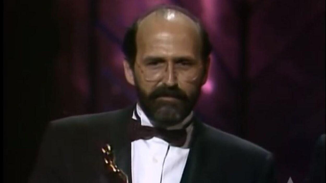 Un homme qui tient une statuette dorée en parlant sur une scène.