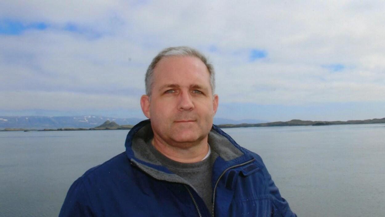 Paul Whelan, devant une étendue d'eau, regarde la caméra.