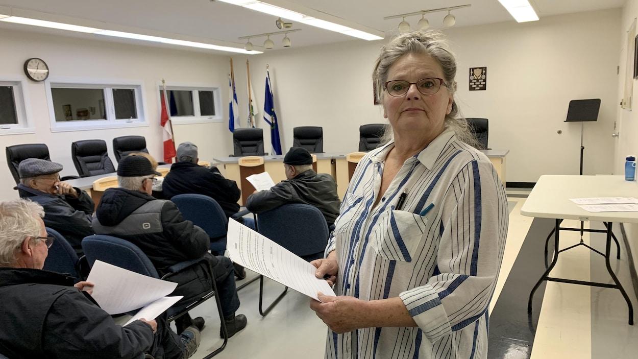 La dame debout dans la salle du conseil municipal avec la pétition dans les mains.