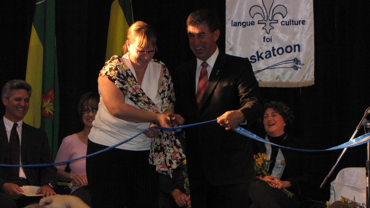 Une femme et un homme coupent un ruban pour symboliser l'ouverture de l'école.