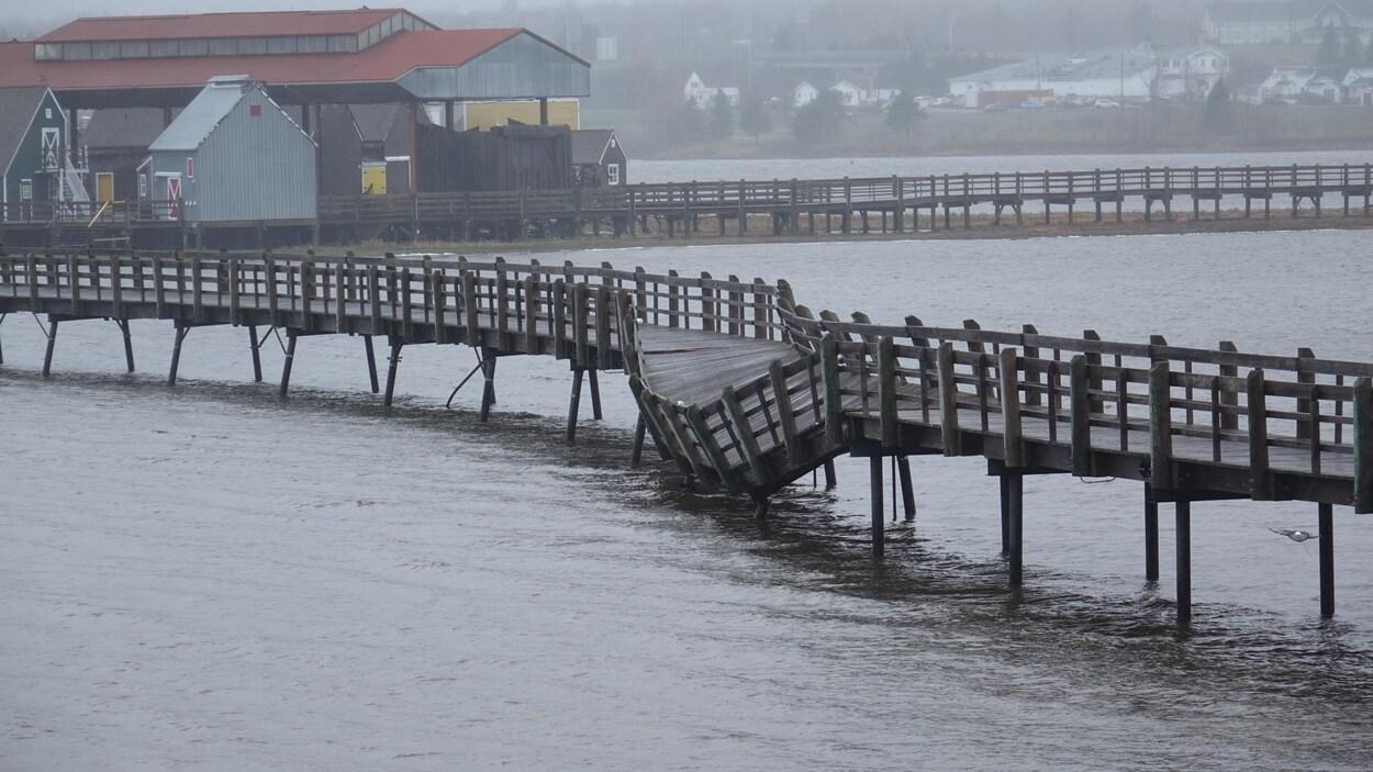 Une section d'une passerelle en bois traversant un plan d'eau a basculé sur le côté.