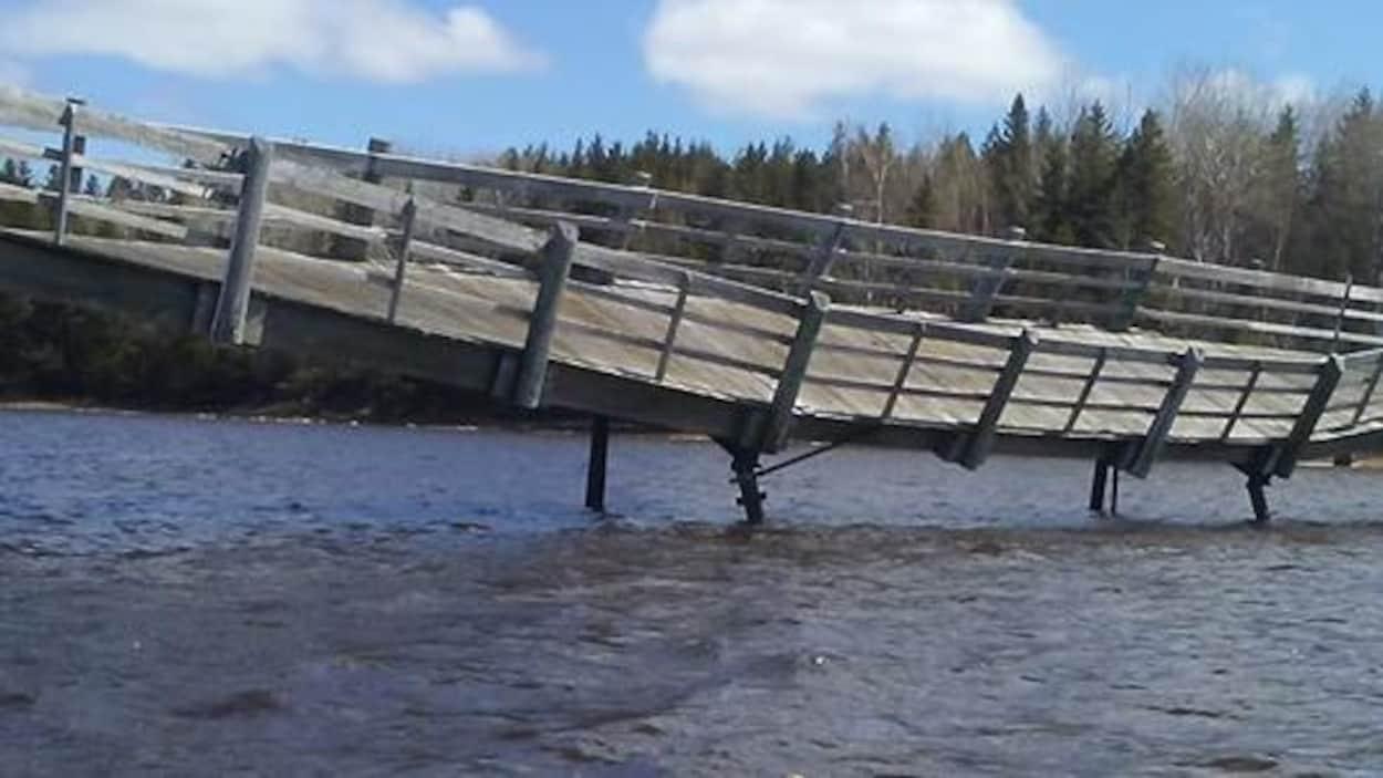 La passerelle du Pays de la Sagouine inclinée vers l'eau avec un kayak à l'avant-plan.
