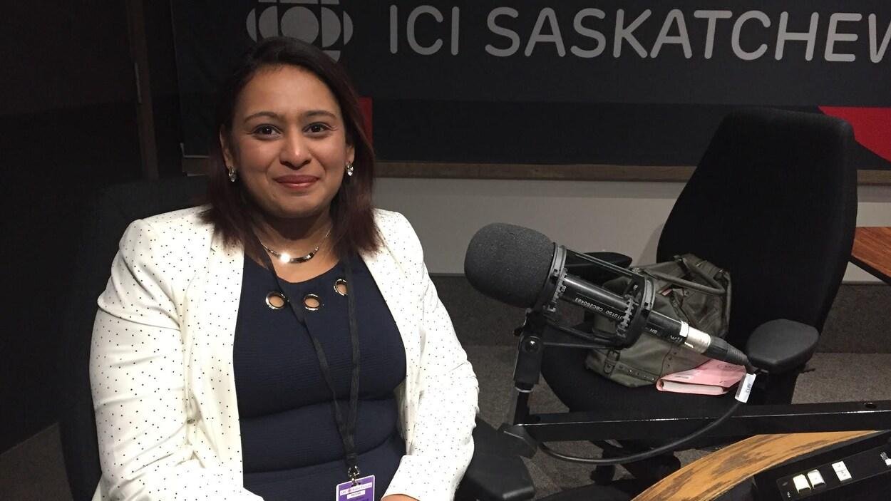 Une femme porte un veston. Elle sourit à la caméra, devant un micro de radio.