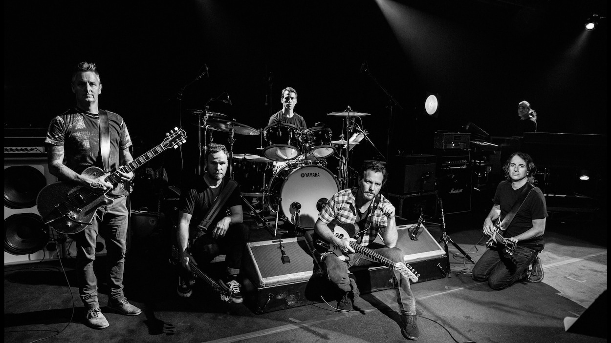 Photo en noir et blanc sur laquelle cinq musiciens sont photographiés avec leurs instruments.