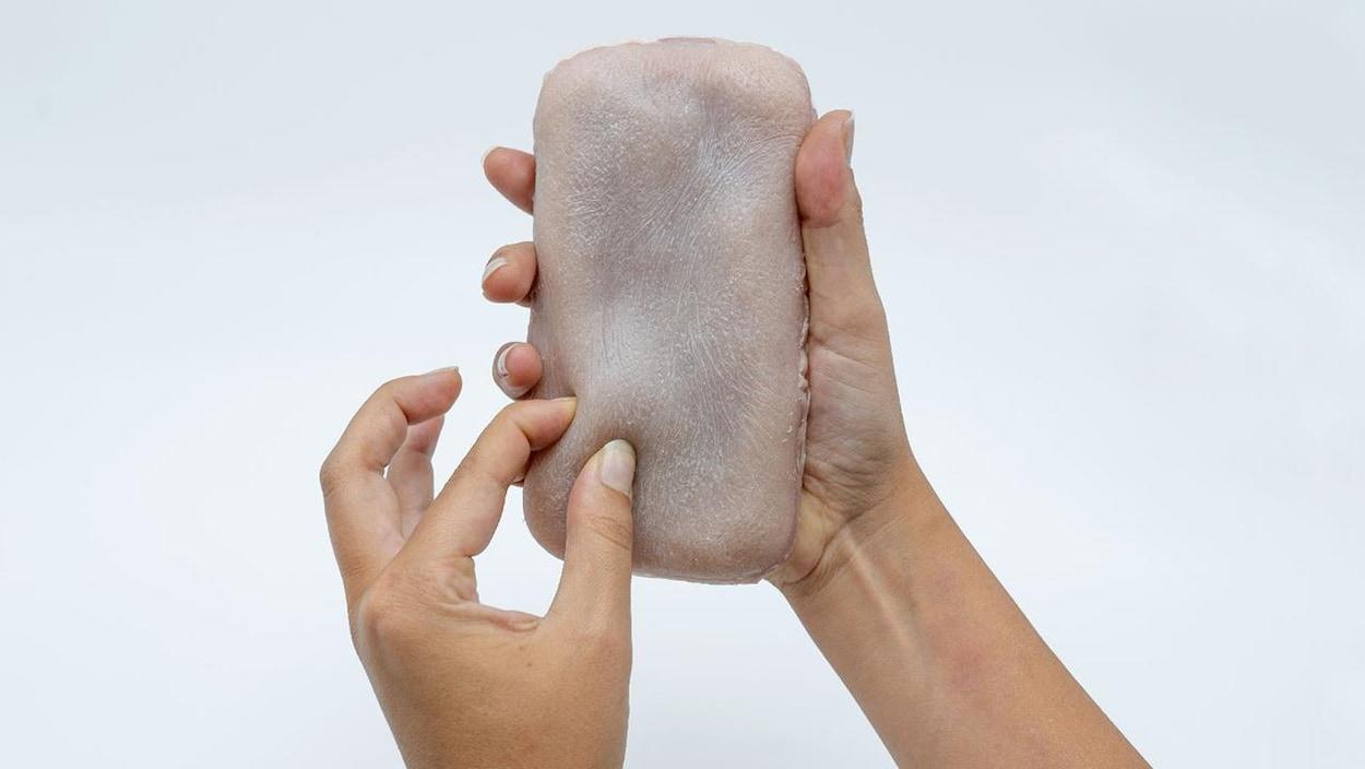 Des mains tiennent un iPhone recouvert d'une membrane ressemblant à de la peau humaine.