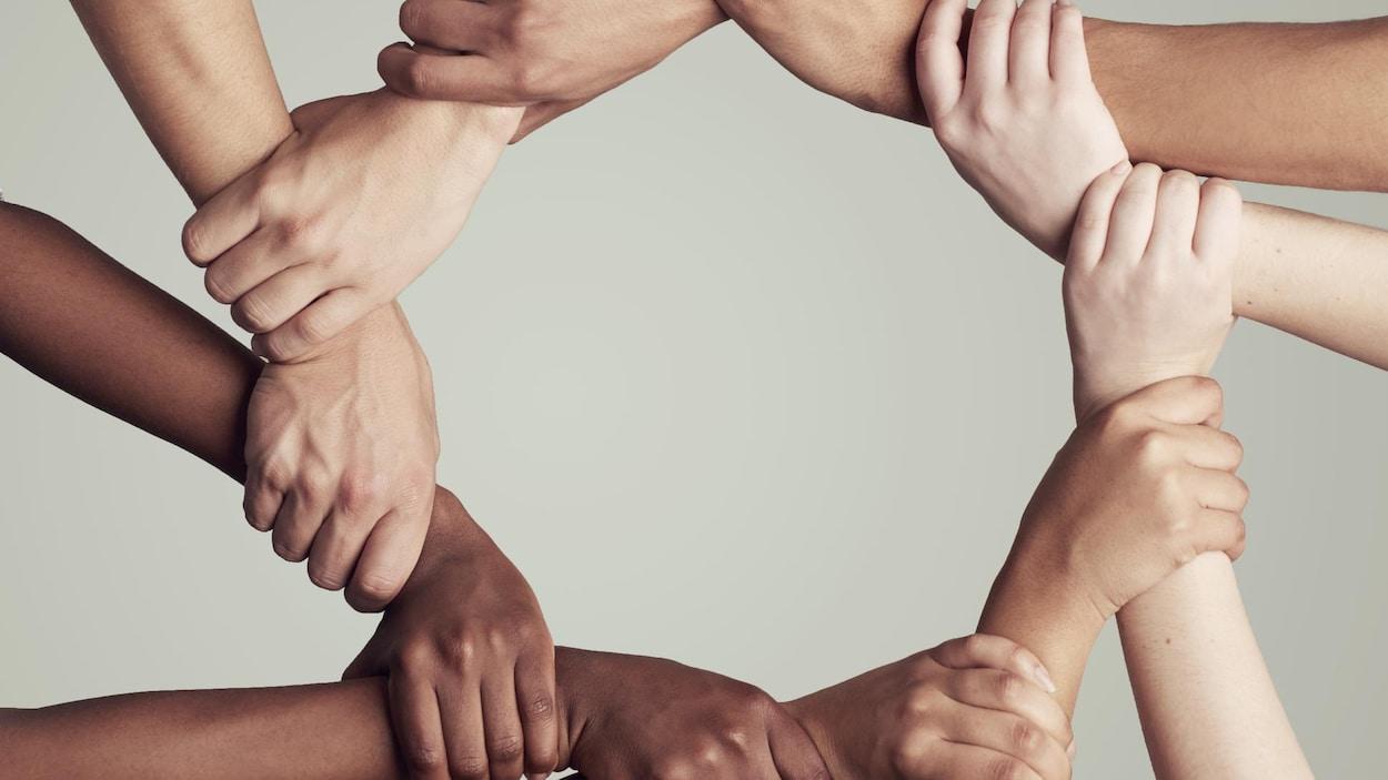 On voit des bras de femmes de différentes origines se tenir les uns les autres pour former un cercle, vu de haut.