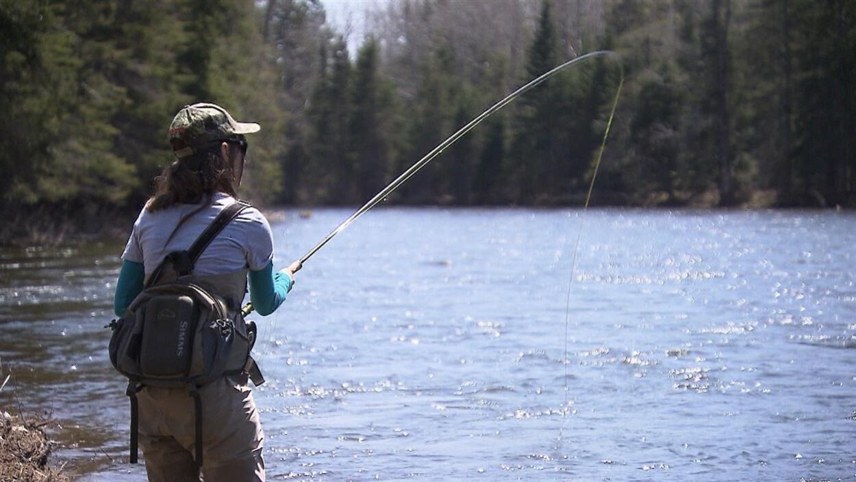 Une pêcheuse dans une rivière lance sa ligne à l'eau.