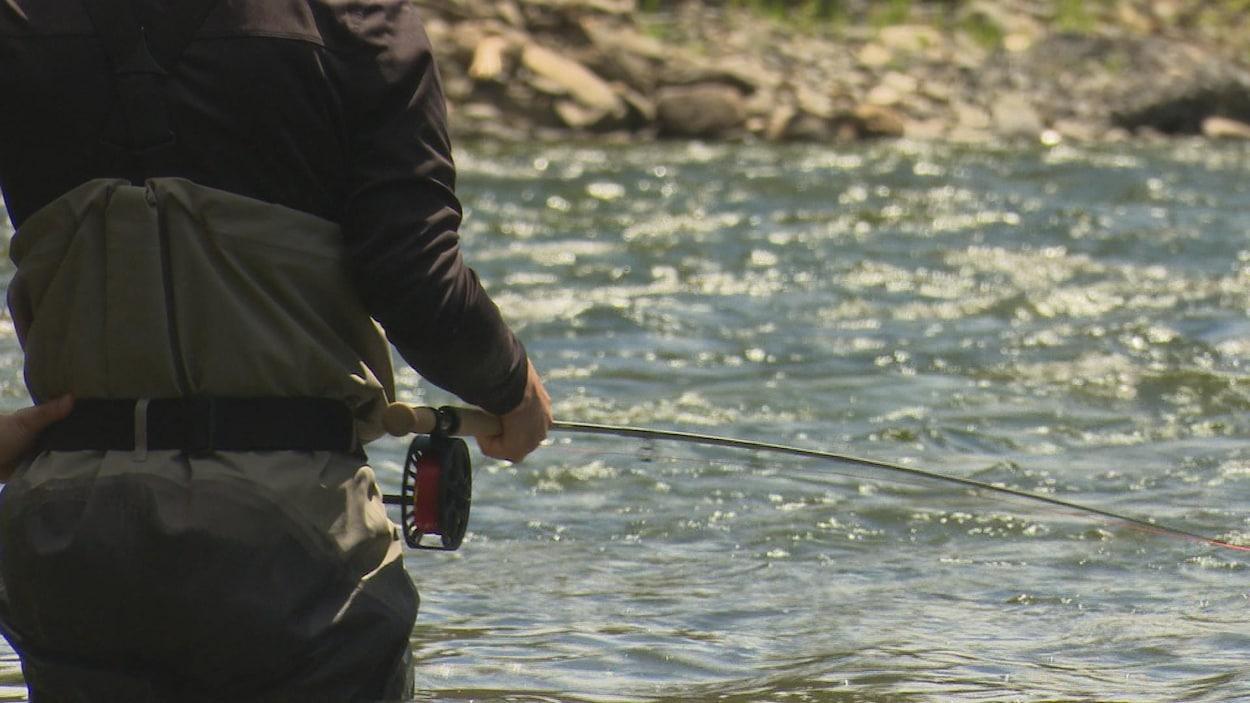 Un homme, que l'on voit de dos, pêche dans une rivière.