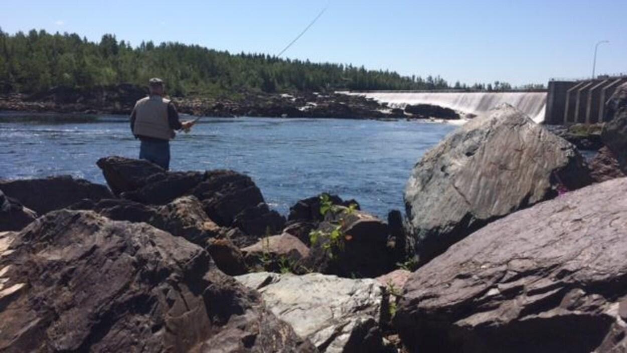 Un pêcheur de saumon lance sa ligne à l'eau dans une rivière.