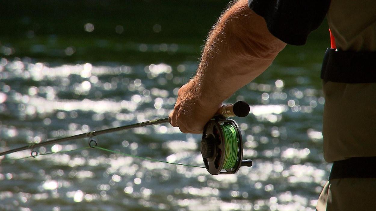 Une canne à pêche au saumon dans la main d'un pêcheur.