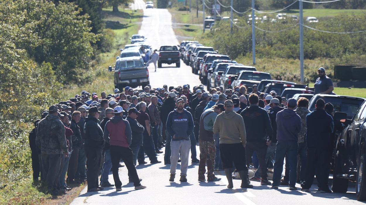 Des dizaines d'hommes manifestent sur une route.