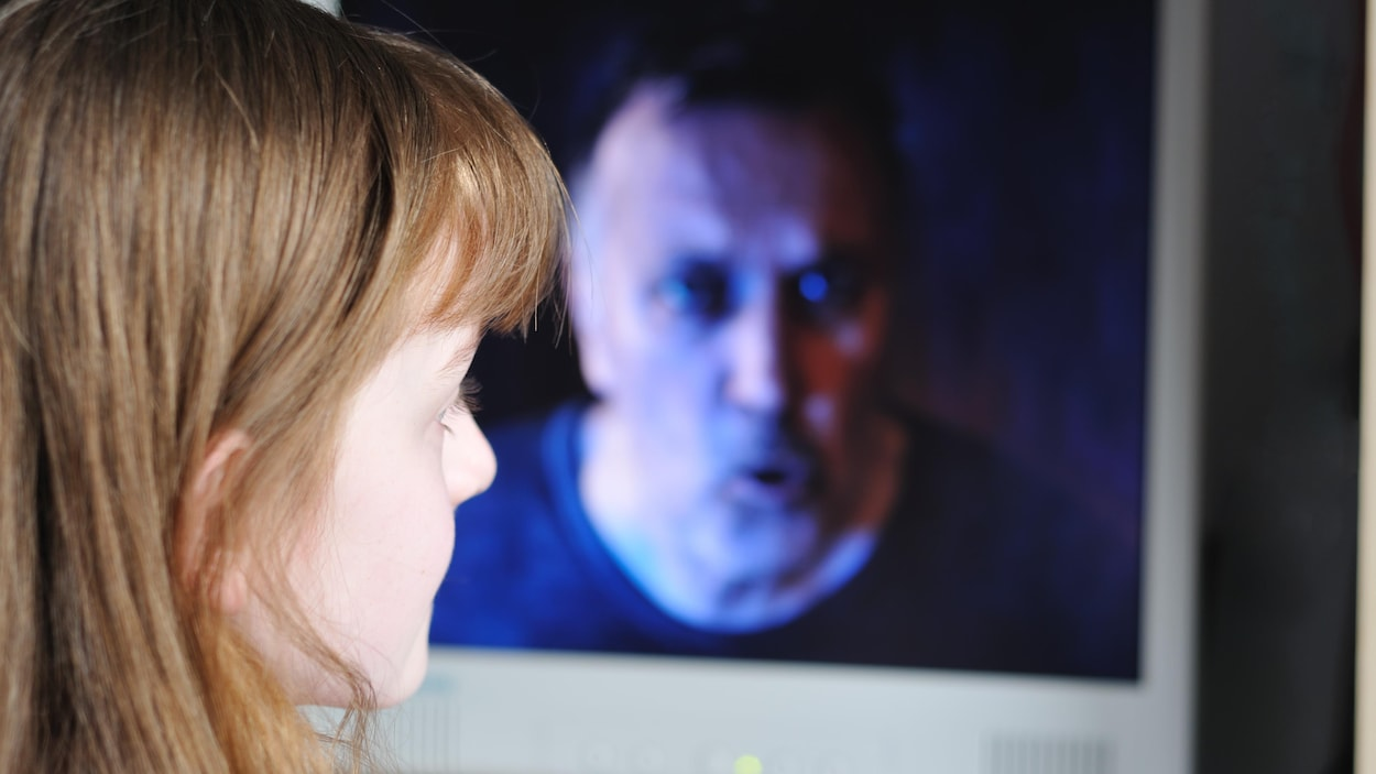 Une enfant regarde un homme menaçant sur un écran d'ordinateur.