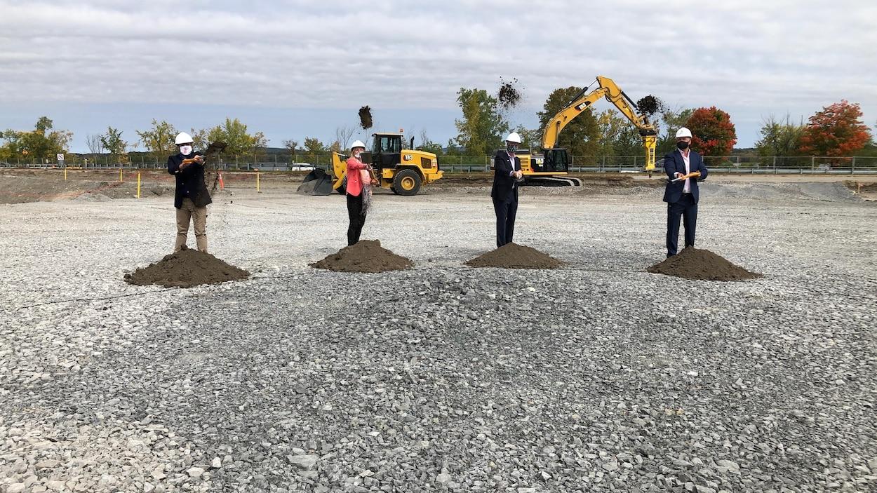 Quatre personnes participent à une pelletée de terre
