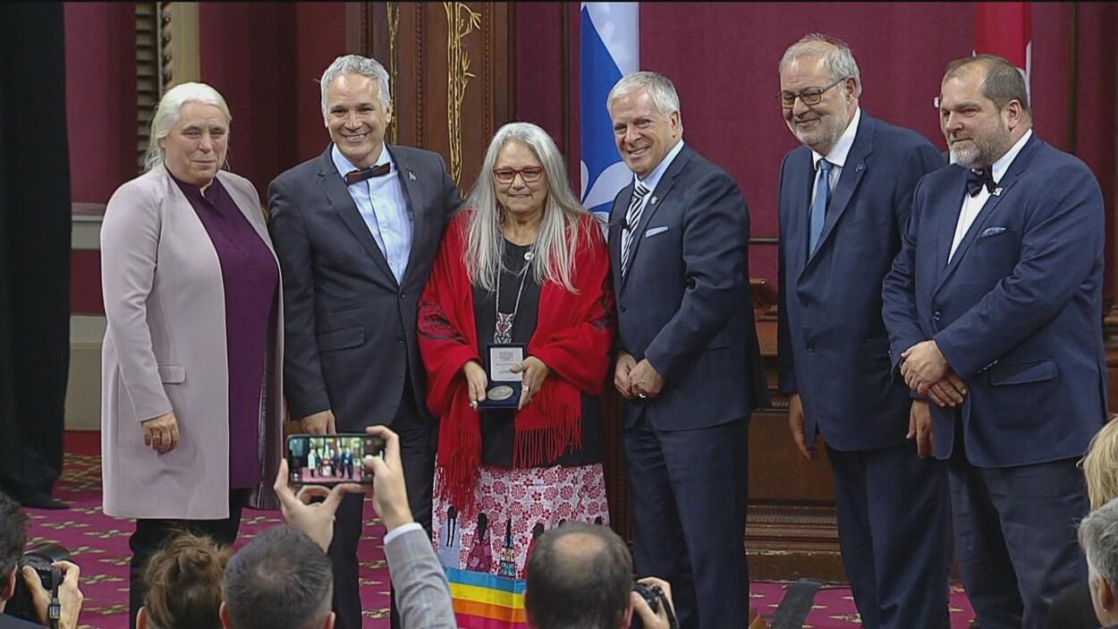 Pénélope Guay, tenant sa médaille dans ses mains, entourée de députés à l'Assemblée nationale.