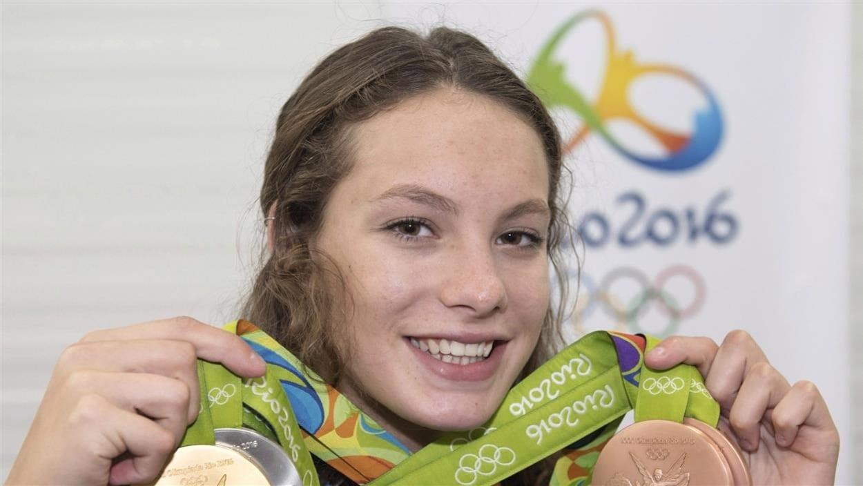 Penny Oleksiak pose avec quatre médailles, avec un grand sourire