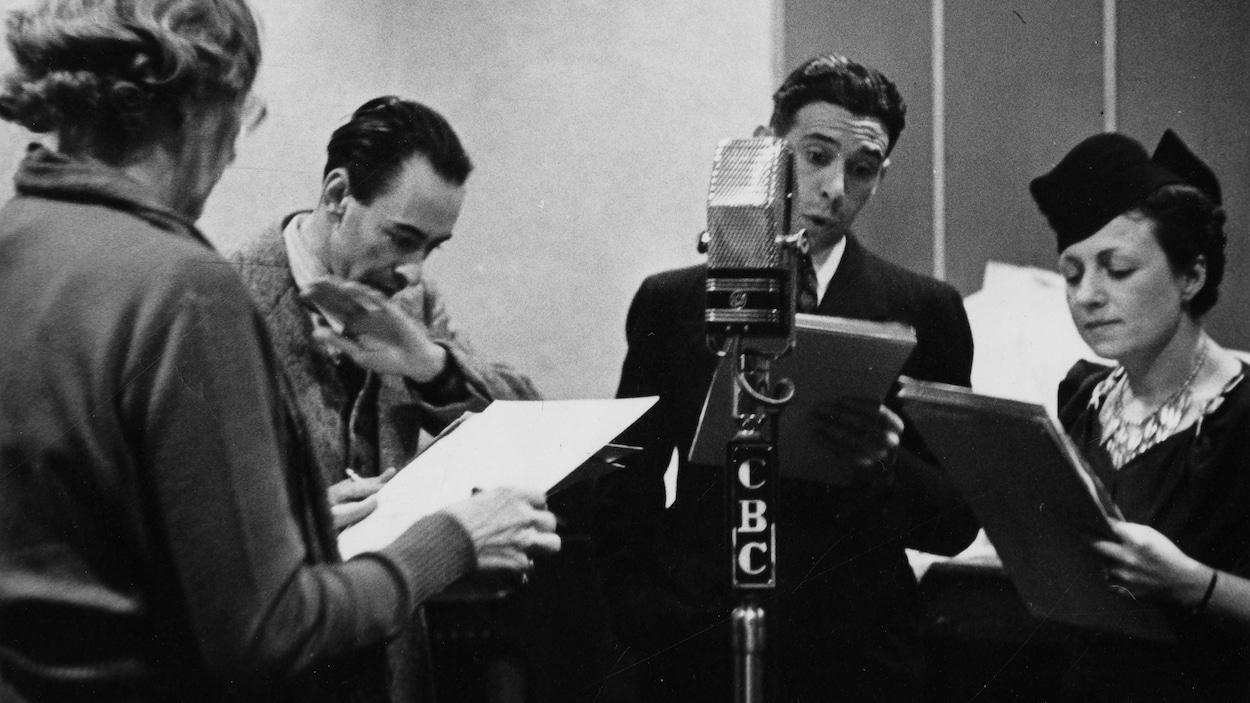 Dans un studio de radio, autour d'un microphone sur pied, la comédienne Jeanne Maubourg, l'auteur Robert Choquette, les comédiens Clément Latour et Berthe Lavoie.
