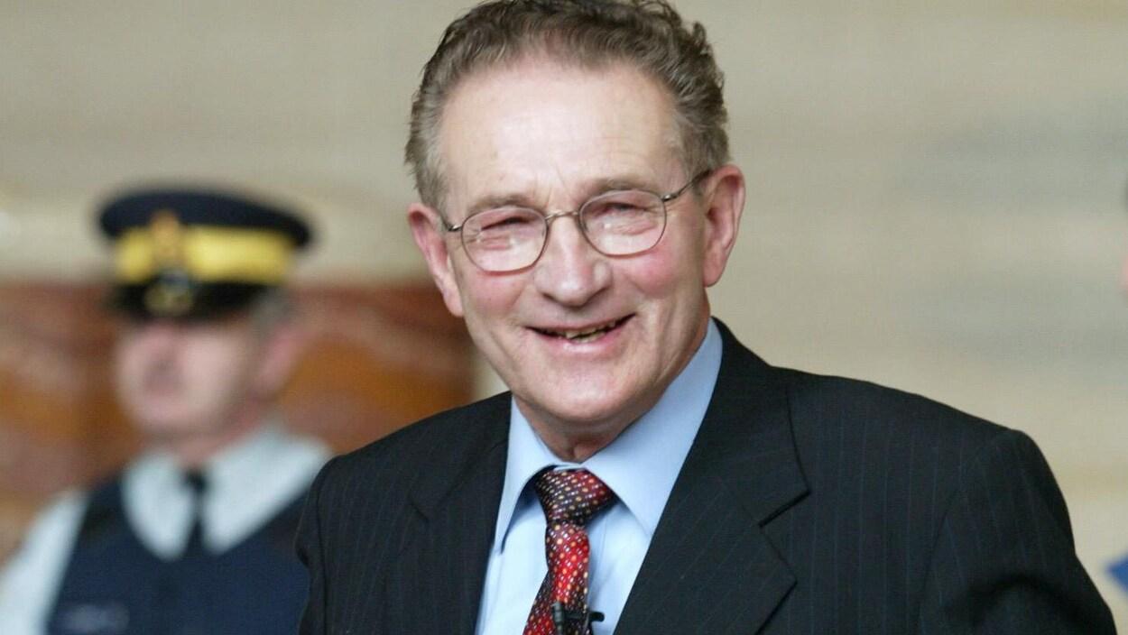 Plan serré de Percy Schmeiser en costume cravate qui sourit. En flou en arrière-plan : un agent de la GRC.