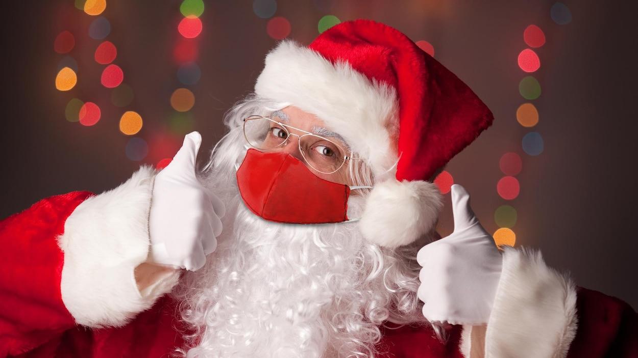 Un père Noël qui porte un masque rouge.