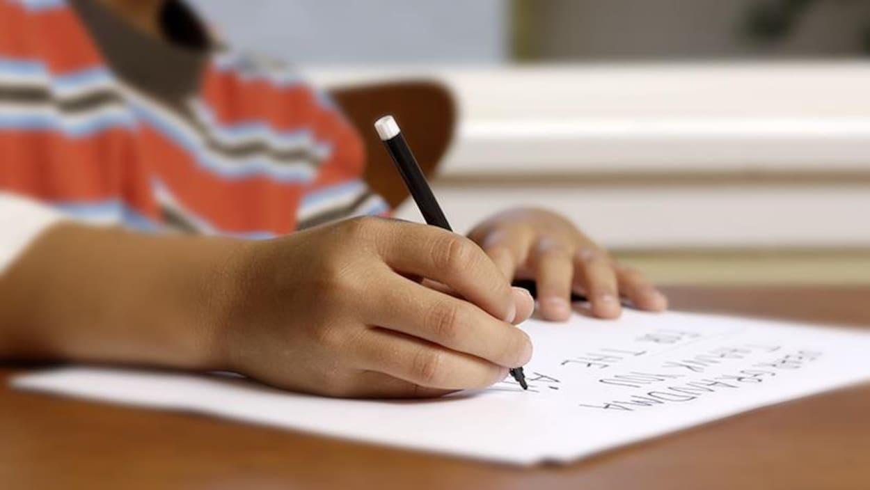 On voit les mains d'un enfant qui écrit sur une feuille.