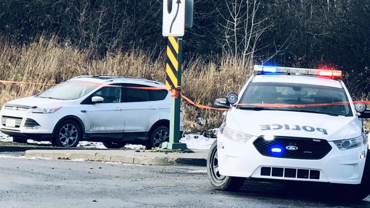 Une voiture de police est stationnée près d'un autre véhicule.