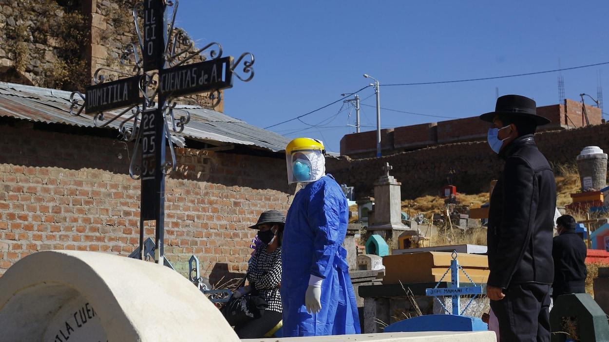 Un travailleur de la santé en habit de protection dans un cimetière autochtone au Pérou.