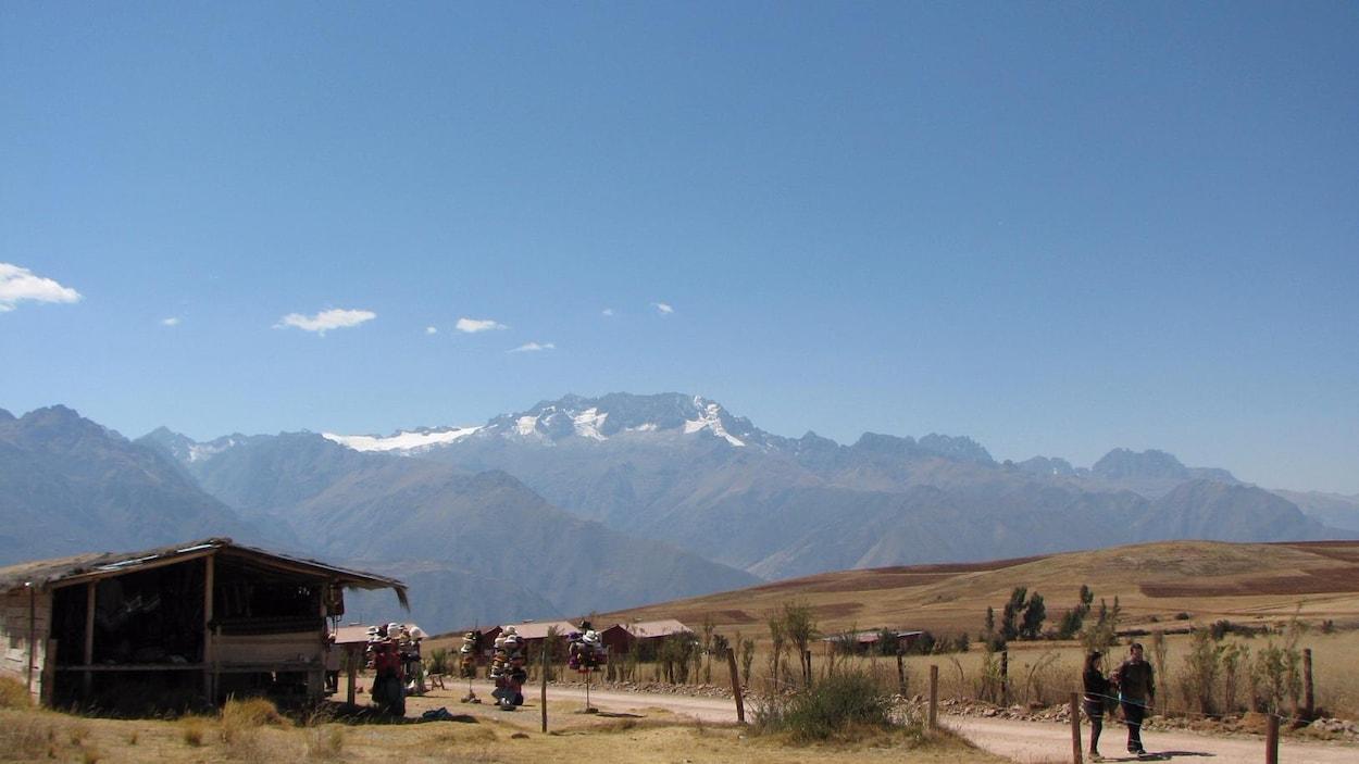 Un paysage vallonneux et sec entouré de hautes montagnes.