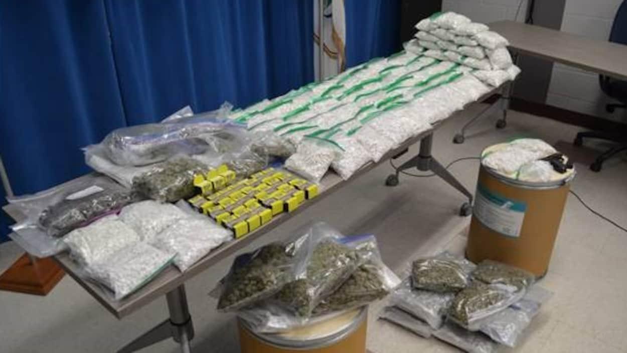 Les drogues saisies lors de la perquisition sont étalées sur une table.